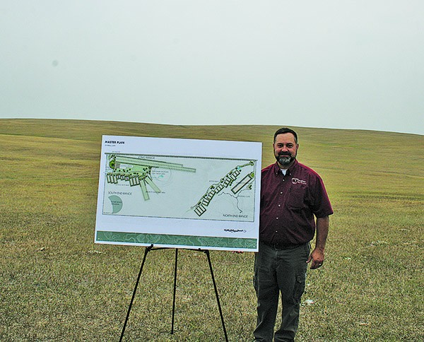 — John Kanta, terrestrial section chief for S.D. Department of Game, Fish & Parks shows off the rendering of the new Rapid City Firearms Complex. The natural topography of the land behind Kanta will capture the ammunition marksmen will use and make for a stunning backdrop for all types of shooters. [PNPhoto/Leslie Silverman]