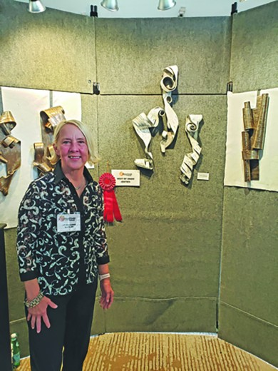 Lenore Lampi poses in front of her second place award winning piece, which resembles birch bark peeled off a tree, at the 12th Annual Sculpture in the Hills Show and Sale in 2019. Due to Covid the show and sale was canceled in 2020, but this year it is back this weekend, June 18-21, downtown Hill City.