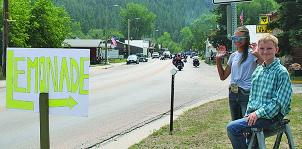 — Taya Skogen waves to motorists as her friend Trey Sutherland mans the stool with a smile. The children enjoyed selling lemonade during the rally to help motorcyclists cool off and beat the heat. This is the 2nd year in a row the young go getters have had a lemonade stand during bike week. [PNPhoto/LESLIE SILVERMAN]