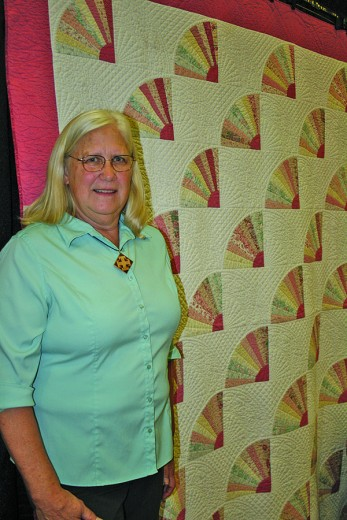— Fan of quilting, Mary Kay Cole, the Hill City Quilt Show featured artist stands in front of one of the first quilts she made. Cole got into quilting in the late 1980's after being involved in sewing and needlework most of her life. Quilting allowed her to repurpose old clothes and give new life to fabric that would have otherwise been discarded. [PNPhoto/Leslie Silverman]